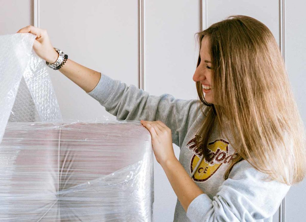 A woman unwrapping her furniture after moving house